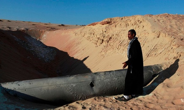 A Bedouin man looks at a gas pipeline that was hit by a RPG in North Sinai